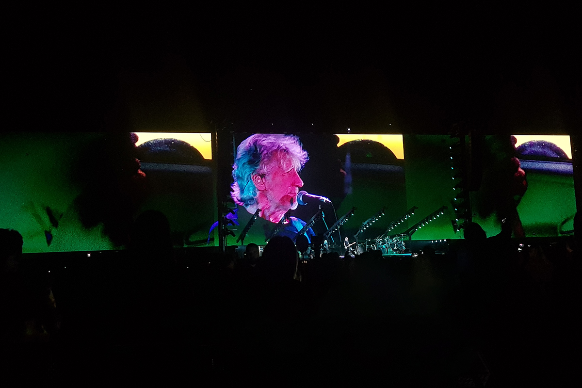Roger Waters cantando para um estádio lotado.